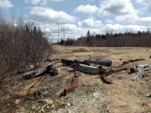 Broken up tractor sled parts on a pole line near Grand Falls. This appears to be a pretty big sled. Hundreds of these large sleds were constructed and use d each year to be used in the annual haul off. A tractor sled could load a number of cords whereas horse sleds were smaller. Caterpillar tractors were first used by AND Co during the early 1920s and by the 1940s had become an integral part of the wood hauling process.