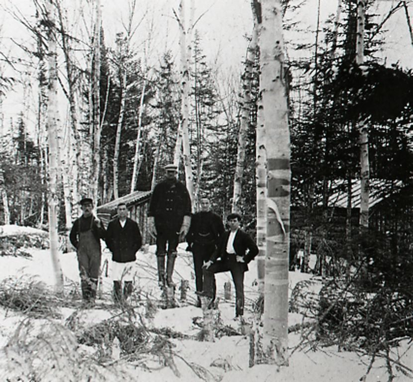"""Construction camp of the Botwood Railway, between Grand Falls and Bishop's Falls, 1908. Origional caption says: Botwood Railway Construction. 4.5 miles from Grand Falls. 1907. List of names says """"L-R: N. Powell (Carbonear Chainman), J. Parsons (Carbonear Cook), R. J. Kennedy (Holyrood Superintendent), P. Gruchy (Grand Falls Cost Accountant)""""(GFCRR).   Built just ten years after completion of the Newfoundland Railway many of the men who built the Botwood Railway had worked in putting the main line across the island. (GFWHS)"""